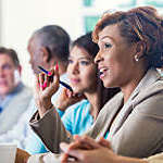 Mid adult African American businesswoman is answering a question during a job training seminar or business conference. She is wearing business casual clothing and holding a pen. Woman is sitting with diverse professional colleagues.