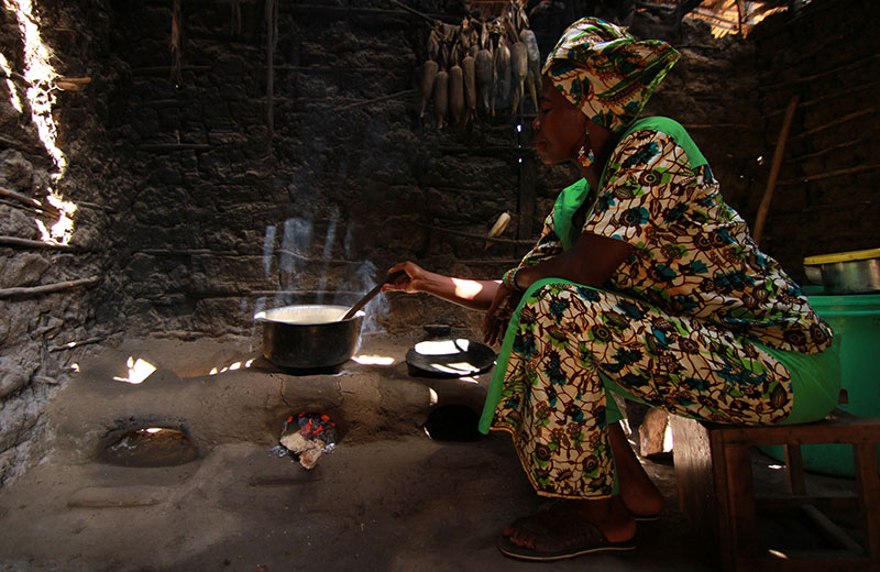 African woman in a hut, cooking in a cookstove