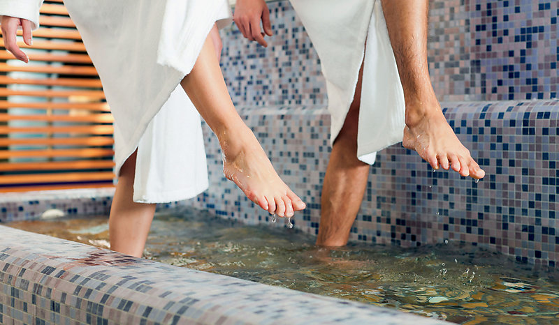 Close-up of a womand and a man's feet in the bath of a SPA