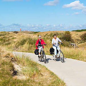 Two senior women cycling in dunes, Texel, Netherlands.