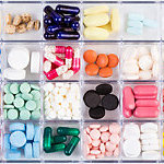 Various medicine pills and capsules in a plastic pill organizer.