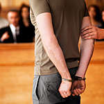 Handcuffed man standing in courtroom.
