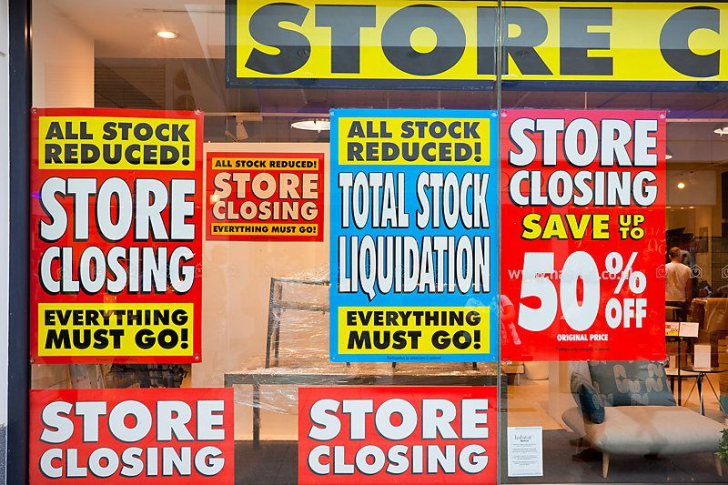 View of a diplay window of a furniture store with posters of total stock liquidation and big discounts due the imminent closure.