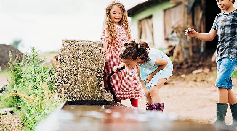 Farmer's children drinking water from a hose.