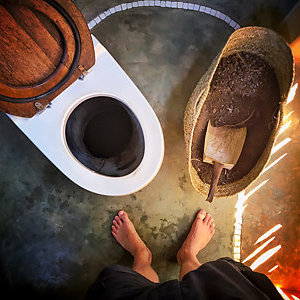 The feet of a man standing in front of an eco-friendly dry toilet.
