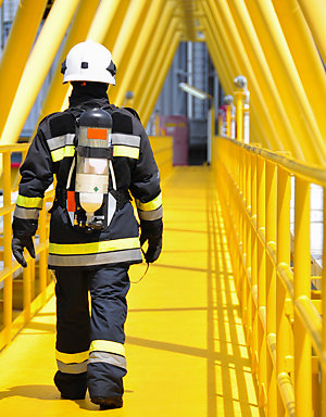 Back view of a fire fighter walking on a bridge.