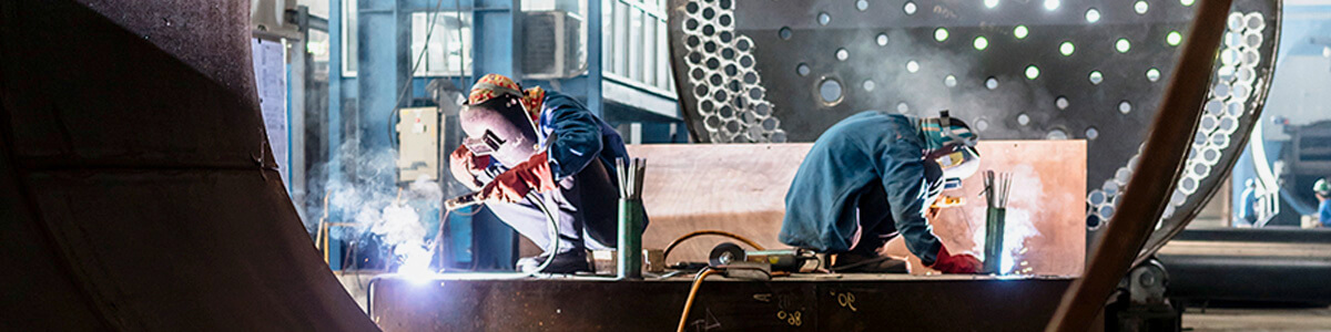 Two workers welding in a factory.