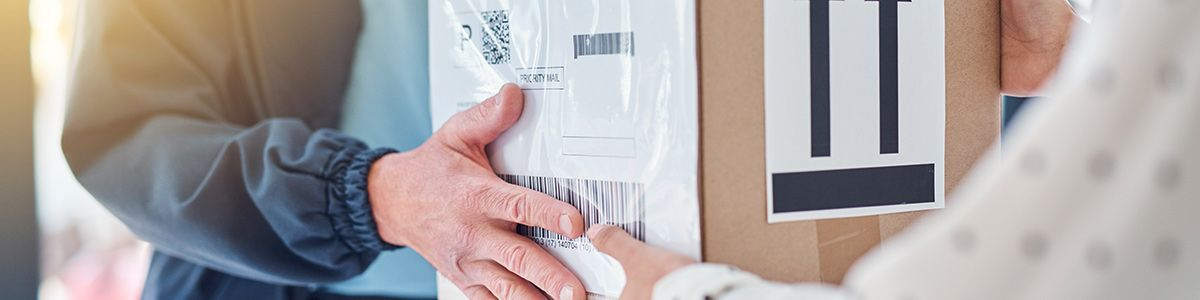 Cropped shot of the hands of a delivery man handing a package to a female customer.