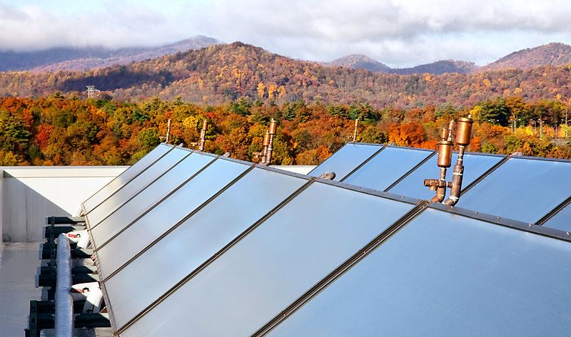 Rooftop view of solar panels against a colourful autumn landscape.