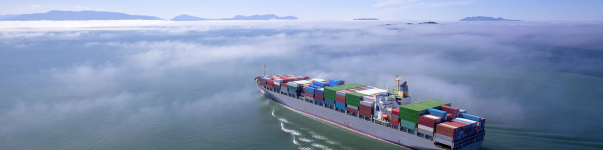 Aerial view of a container ship sailing through the fog.
