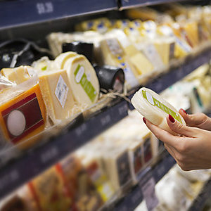Hands of a woman checking the label of a packaged cheese in a supermarket.