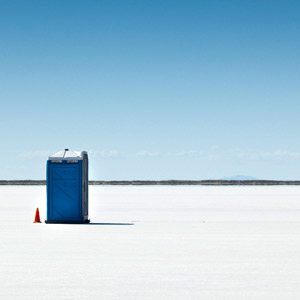 Blue portable toilets on the textured ground in Bonneville Salt Flats, USA.