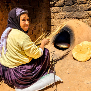Moroccan woman baking bread (khubz) in a clay oven.