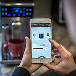 Hands of a man a coffee application on a mobile phone with an application used to control the bluetooth coffee machine.