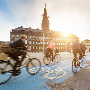 Blurred people going by bike in Copenhagen, with Christiansborg palace on background.