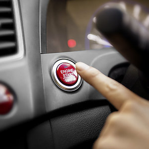 Closeup - finger pressing car engine start button.