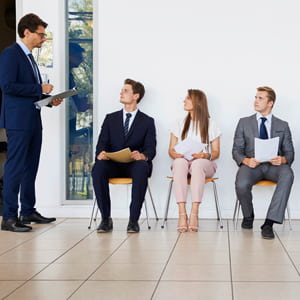 A recruiter and 5 people waiting for job interviews.