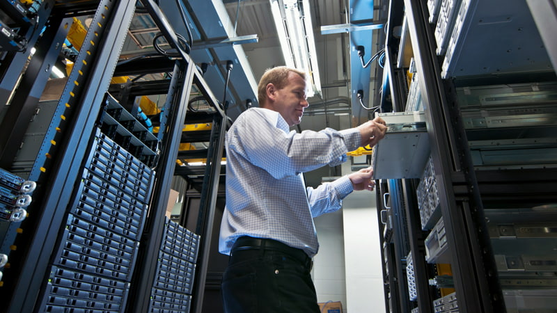 IT administrator installing a new rack mount server.