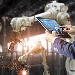 Manager industrial engineer using a tablet to control welding robot arms machine.