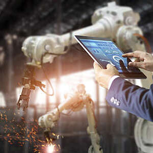 Man in a suit controls the arms of a welding robot from his tablet.