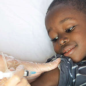 Close-up of a little black boy smiling as he receives a vaccine.