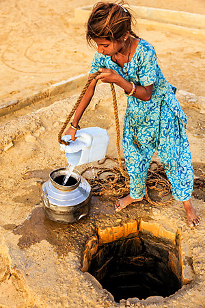 A young Indian girl fills a metal container with water from a well.