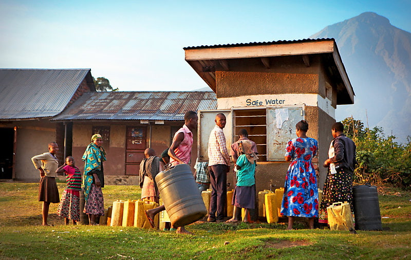 Local villagers waiting with plastic canisters to get safe water from a public water well.