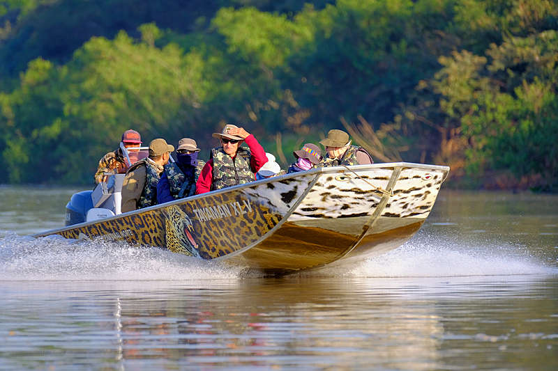 Tourists, pilot and guide on a boat excursion, Pantanal, Brazil.