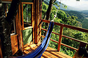 Relaxing scene with a hammock on the balcony of a treehouse offering a beautiful view over a tropical valley.