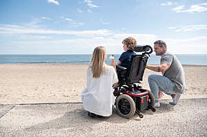 Parents kneeling by a 6 year old boy in a wheelchair, enjoying an ice cream on the beach, while looking at the view.