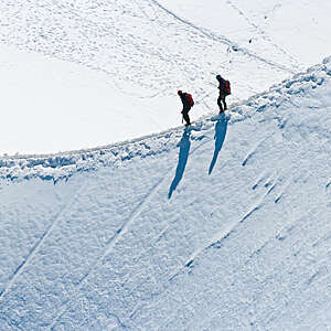 Alpinists roped together to climb along a narrow snow arete in bright sunshine high on Mont Blanc in the French Alps.