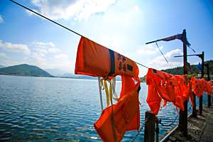 Personal flotation devices hang to dry on a line on pier.
