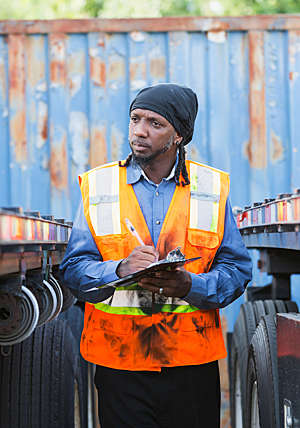 A man wearing a safety vest and taking notes, is standing between two semi trucks.