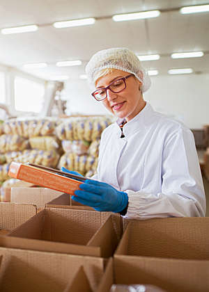 Smiling female worker in sterile lab coat packs finished food products in boxes in a food factory.