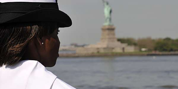 US Navy female sailor gazing at the statue of liberty in New York, USA.