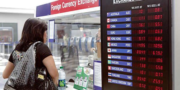 Woman exchanges money at a currency exchange kiosk at Chicago's O'Hare International Airport.