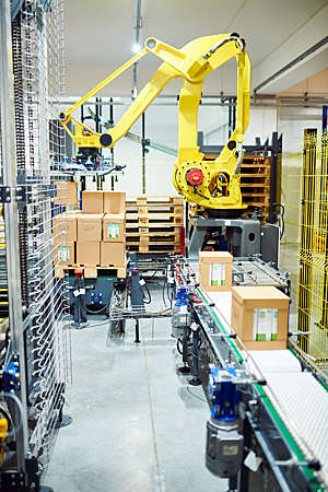 Industrial robotic arm picks cardboard boxes off a conveyor belt in a warehouse.