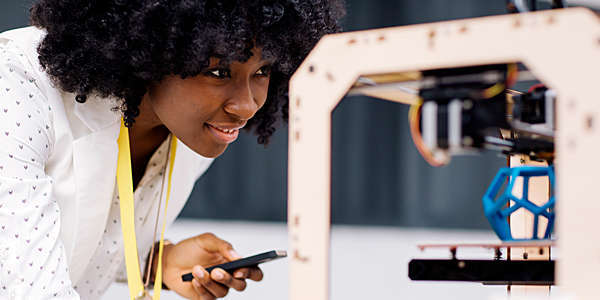 Woman holding her smartphone and printing on a 3D printer.