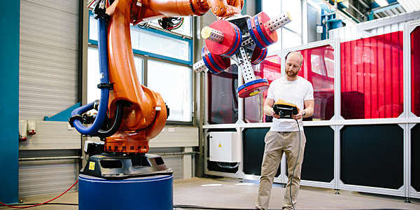 Engineer works a robotic arm from a tablet.