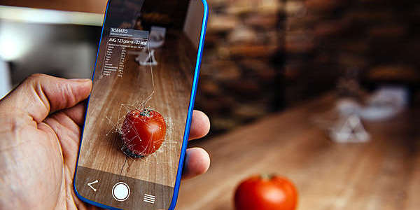 Hand holding a smartphone displaying augmented-reality image of a tomato.