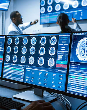 Medical scientists discuss CT brain scan images on a computer screen.