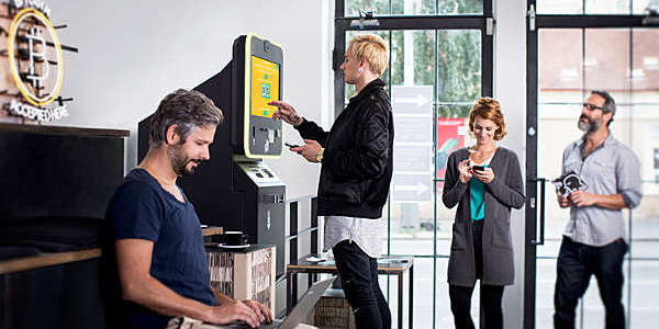 People standing at a Bitcoin ATM to buy cryptocurrencies.