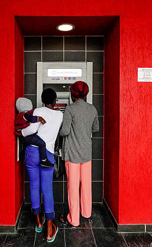 Rear view of two women, one carrying a child, withdrawing money from a cash machine in Namibia.