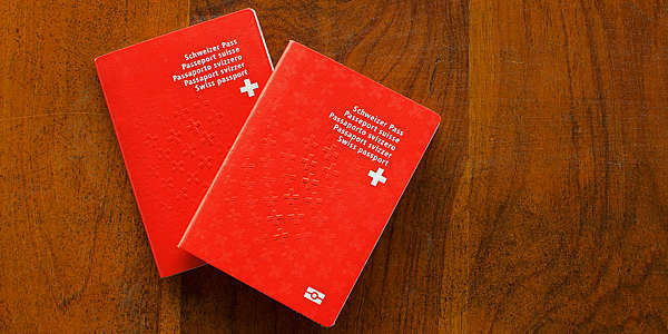 Top view of two Swiss Passports on a wooden table.