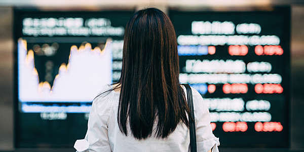 Back view of woman looking a stock exchange screens.