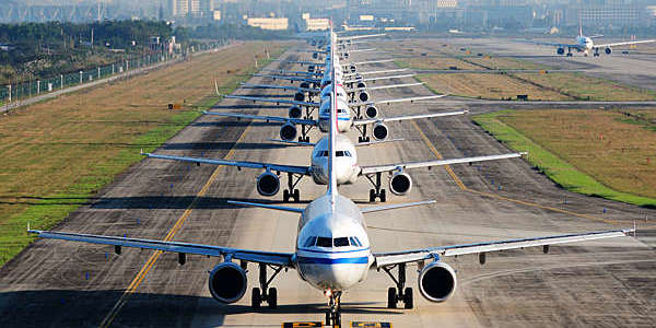 Airplanes line up on runway for departure.