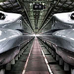 Two Japanese Shinkansen high-speed trains with vanishing view of station platform.