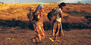 Two African women carrying terracotta water pots on their backs.