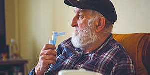 Elderly man using an inhalation mask.