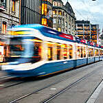 Blurred view of blue and white tram speeding across a city centre.